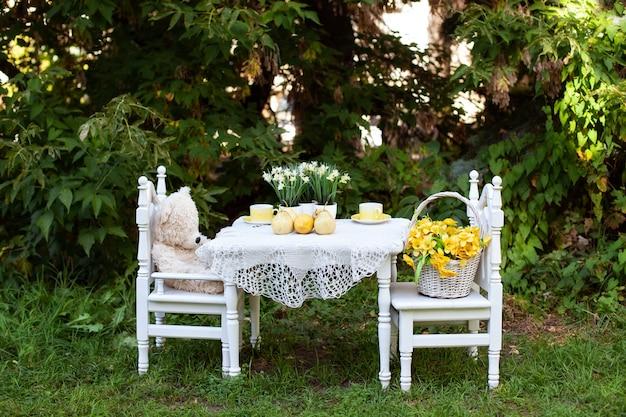 Toy teddy bear-zitting op witte stoel en kop theeën bij de witte kleine lijst. kinderspeelplaats in de tuin. buiten houten stoelen en kind tafel met speelgoed voor klein kind op de werf. rustieke stijl