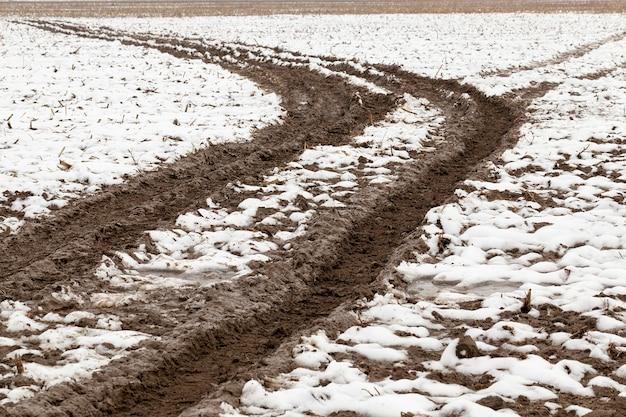 Track en prints in de sneeuw die overblijft van een passerende auto. kleine landelijke weg in de winter. het werd van boven naar beneden van dichtbij genomen.