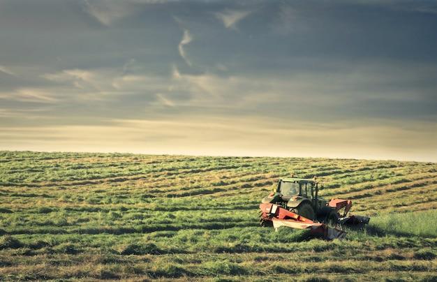 Tractor die aan een boerderij werkt