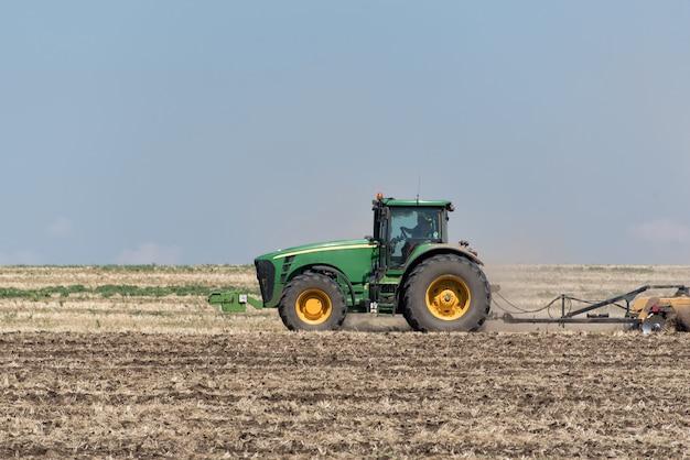 Tractor die de grond ploegt tegen de blauwe hemel