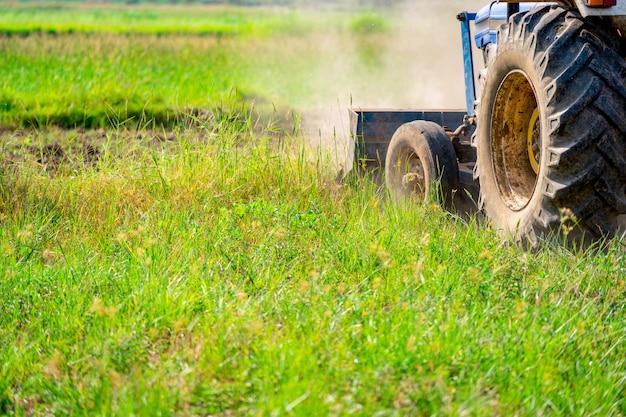 Tractor die op landbouwgebied stromen in landbouwgrond