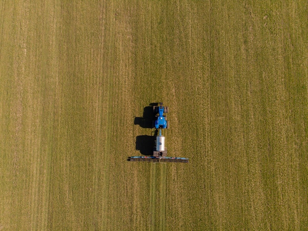 Tractor die vloeibare minerale meststoffen op de grond op de wintertarwe toepassen