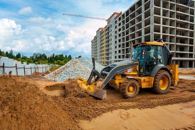 Tractor egaliseert de grond voor de aanleg van een nieuwe weg in de zomer
