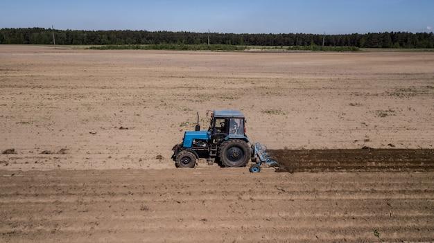Tractor - luchtfoto van een tractor op het werk - cultiveren van een veld in het voorjaar met blauwe hemel - landbouwmachines