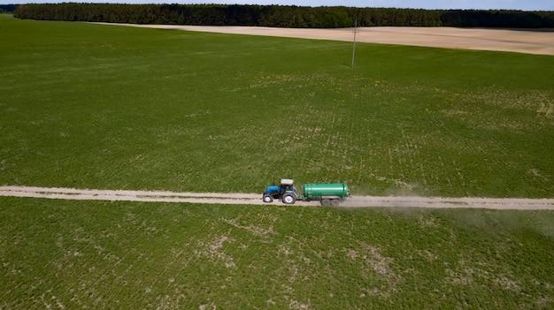 Tractor met aanhangwagenbemestingsveld met natuurlijke mest