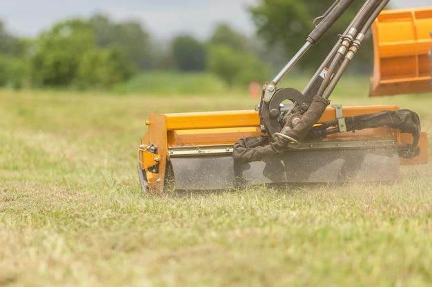 Tractor met een mechanische maaimachine die gras aan de kant van de asfaltweg maait