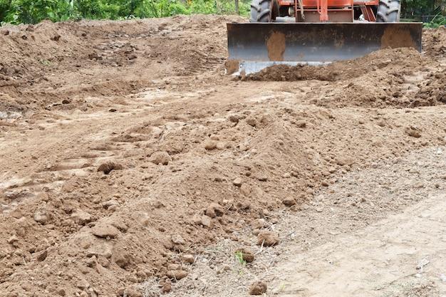 Tractor push stolsel grond na giet van vrachtwagen