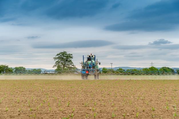 Tractor spuit chemicaliën op het veld voor een betere oogst en ongediertebestrijding. kopieer ruimte