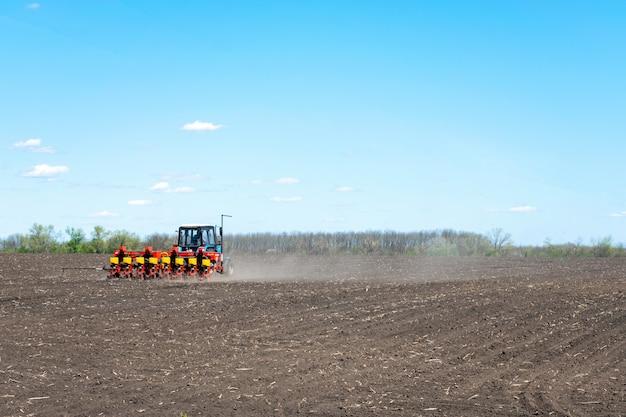Tractor zaait maïs op een geploegd veld