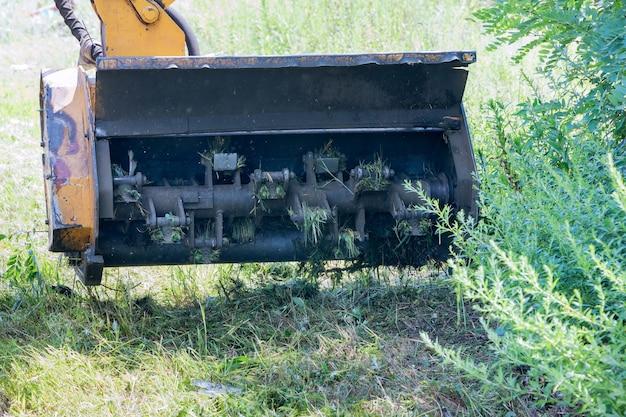 Tractorgrasmaaier op wielen met een externe afneembare gemonteerde maaieruitrusting die langs de weg rijdt van een mechanisatiemachine voor wegenonderhoud in de voorsteden