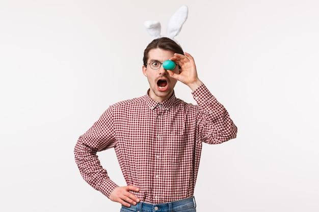 Tradities, religieuze feestdagen, feestconcept verbaasde charismatische jonge bebaarde man in glazen met schattige nep-konijnenoren, open mond verrast, met beschilderd paasei over oog
