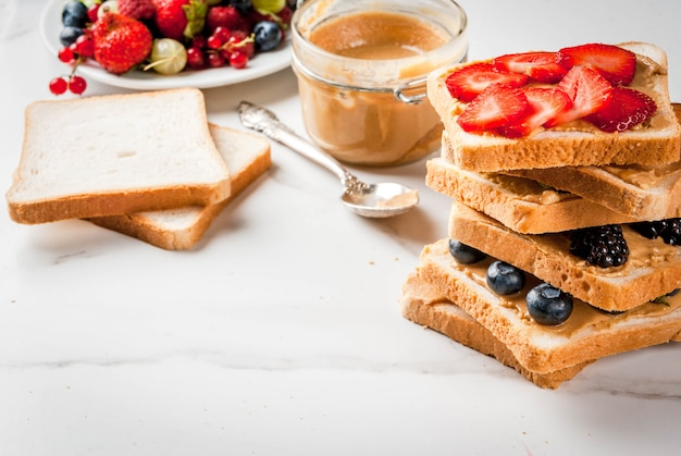 Traditioneel amerikaans en europees zomerontbijt: tosti's met pindakaas, bessen, fruitappel, perzik, bosbes, bosbes, aardbei, banaan. witte marmeren tafel. copyspace