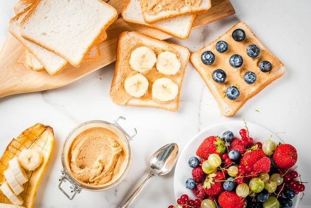 Traditioneel amerikaans en europees zomerontbijt: tosti's met pindakaas, bessen, fruitappel, perzik, bosbes, bosbes, aardbei, banaan. witte marmeren tafel. kopie ruimte bovenaanzicht