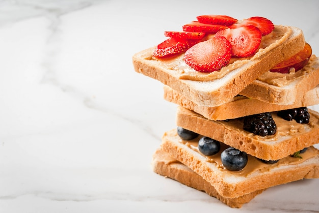 Traditioneel amerikaans en europees zomerontbijt: tosti's met pindakaas, bessen, fruitappel, perzik, bosbes, bosbes, aardbei, banaan. witte marmeren tafel.