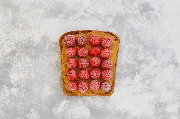 Traditioneel amerikaans en europees zomerontbijt: tosti's met pindakaas, bessen, perzik, vijgen, aardbeien, frambozen, kopie bovenaanzicht