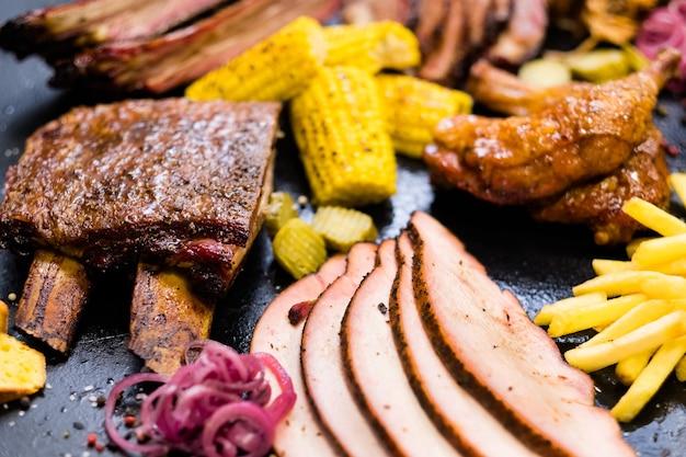 Traditioneel amerikaans eten. gerookt vlees, assortiment gevogelte, frites, gebakken bonduelle mais.