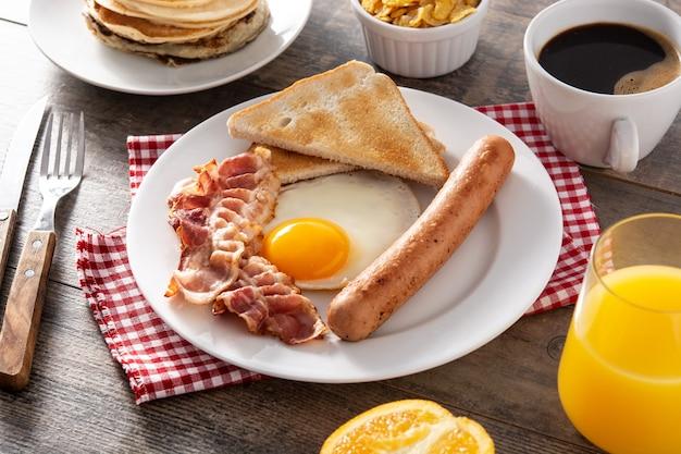 Traditioneel amerikaans ontbijt met gebakken ei, toast, spek en worst op houten tafel