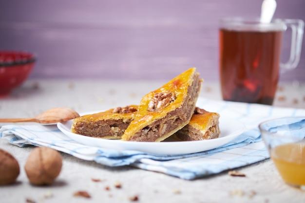 Traditioneel arabisch dessert. baklava met walnoten, kardemom en honing. zelfgemaakte turkse gebakjes. Premium Foto