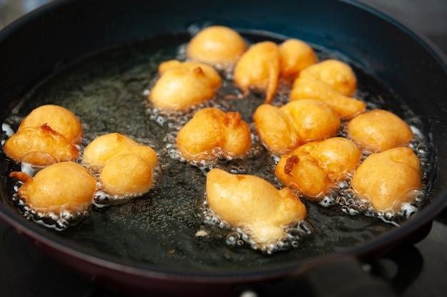Traditioneel braziliaans zelfgemaakt snoepje genaamd bolinho de chuva wordt gebakken in een koekenpan