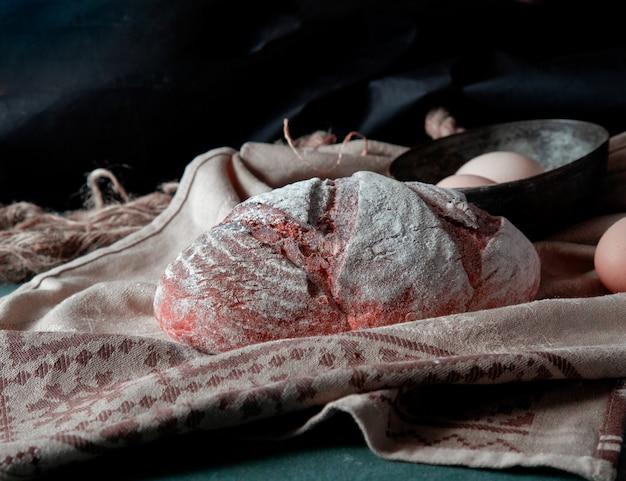 Traditioneel brood met witte bloem erop met eierkom rond op een rustieke handdoek.
