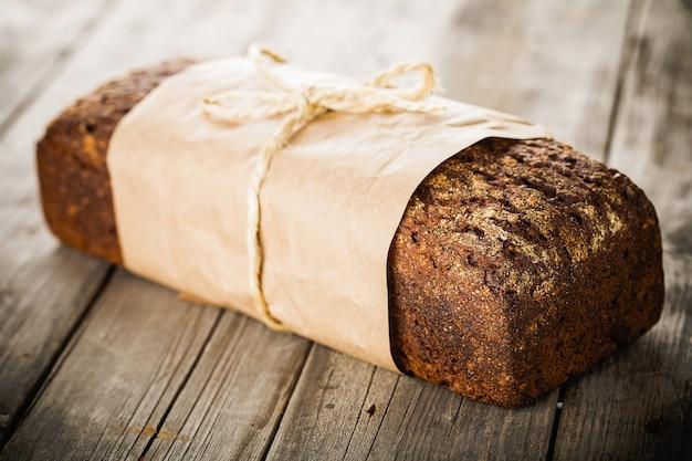Traditioneel brood met zaden verpakt in papier op oude houten tafel