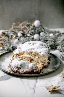 Traditioneel eigengemaakt duits de cakebrood van het kerstmisbaksel op plaat met zilveren kerstmisdecoratie over wit marmeren oppervlakte.