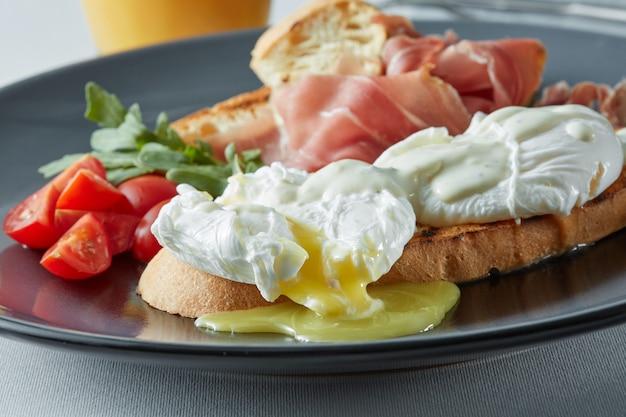 Traditioneel engels ontbijt met benedictus-eieren, toast, tomaten, sinaasappelsap en spek