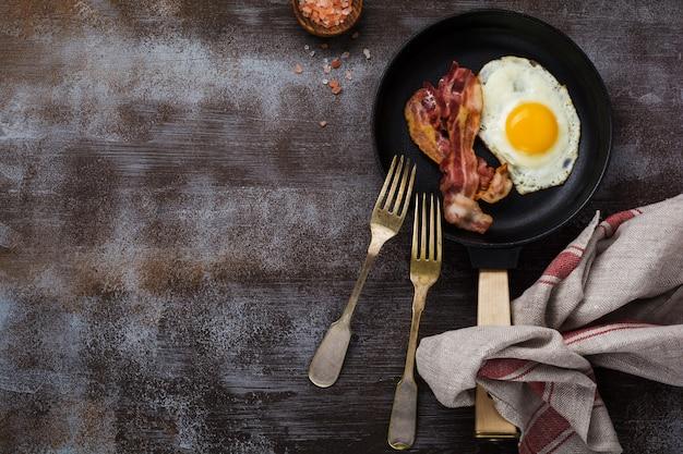 Traditioneel engels ontbijt met gebakken eieren en spek in gietijzeren pan op donkere betonnen ondergrond. bovenaanzicht.