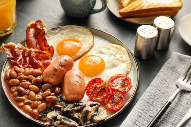 Traditioneel engels ontbijt met gebakken eieren in plaat op donker