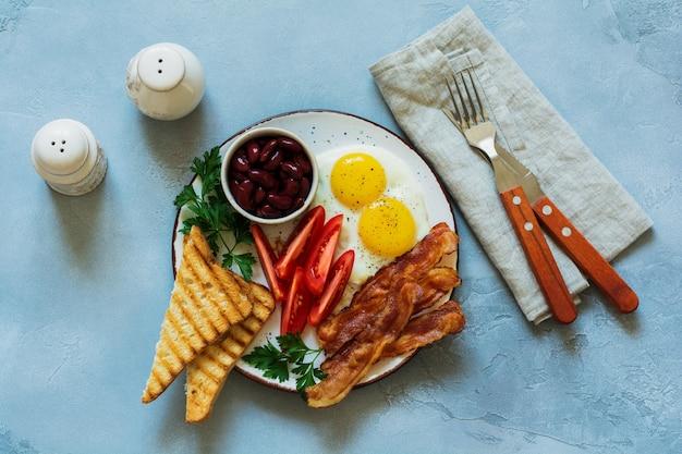 Traditioneel engels ontbijt met gebakken eieren, spek, bonen, toast en tomaten op grijs beton