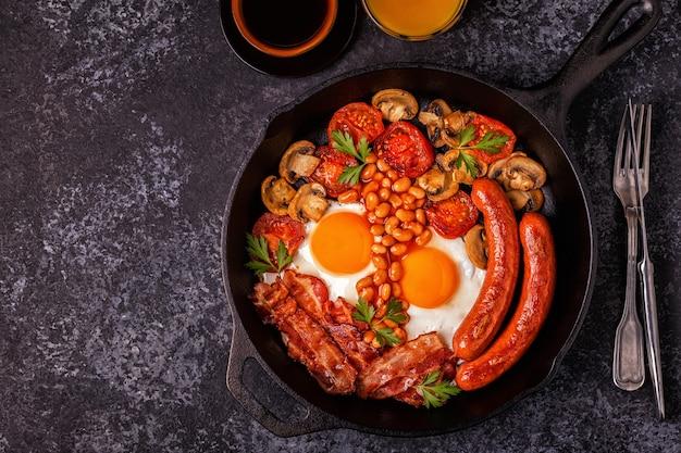 Traditioneel engels ontbijt met gebakken eieren, worstjes, bonen, champignons, gegrilde tomaten en spek.