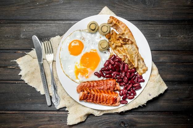 Traditioneel engels ontbijt met gebakken eieren, worstjes en bonen. op een houten tafel.