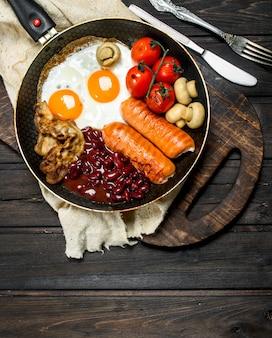 Traditioneel engels ontbijt met gebakken eieren, worstjes en bonen op houten tafel.