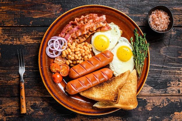 Traditioneel engels ontbijt met gebakken eieren, worstjes, spek, bonen en toast