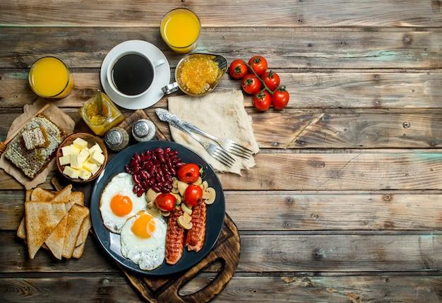 Traditioneel engels ontbijt. snacks met verse koffie. op een houten achtergrond.