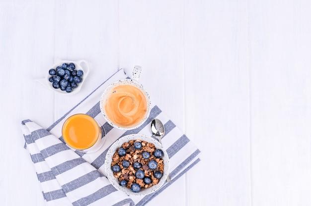 Traditioneel europees ontbijt op witte houten achtergrond. muesli met bessen, koffie en jus d'orange. plat leggen. kopieer ruimte