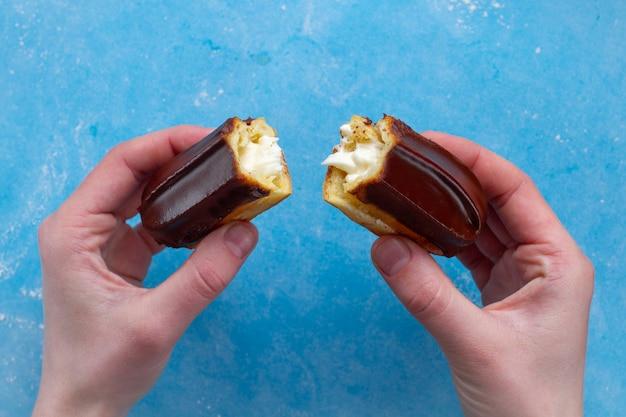 Traditioneel frans dessert. heerlijke eclair met vla en chocoladesuikerglazuur in tweeën in handen gekraakt. gebak, zoet voedsel voor zoetekauw