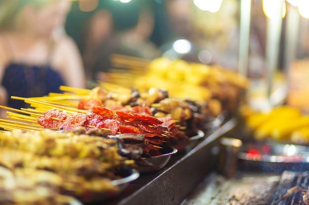 Traditioneel gebraden chinees voedsel op stokken bij straatventermarkt
