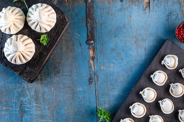 Traditioneel georgisch eten genaamd khinkali en russische zelfgemaakte dumplings. oude houten tafel in blauwe kleur en plaats voor tekst. bovenaanzicht