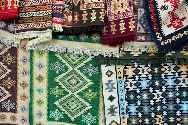 Traditioneel georgisch tapijt. verschillende mooie tapijten liggen naast elkaar. geometrische vormen en patronen.