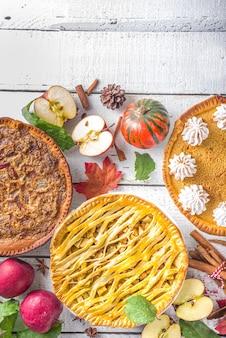Traditioneel herfst bakken. amerikaanse en europese traditionele herfstwintertaarten - met pompoen, pecannoten en appel