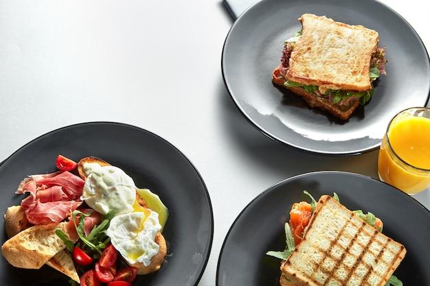 Traditioneel hotel ontbijt geserveerd aan tafel met ham en tomaat, toast, benedictus-eieren, sinaasappelsap