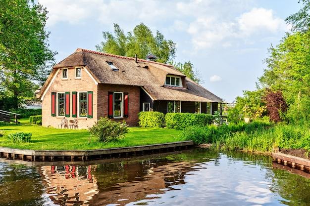 Traditioneel huis met rustiek rieten dak in nederland
