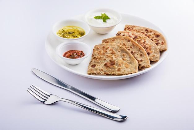 Traditioneel indiaas eten aloo paratha of aardappel gevuld plat brood. geserveerd met tomatenketchup en wrongel over kleurrijke of houten achtergrond. selectieve focus