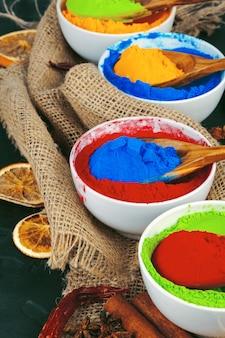 Traditioneel indisch holi-kleurenpoeder, kruiden op donkere rustieke achtergrond