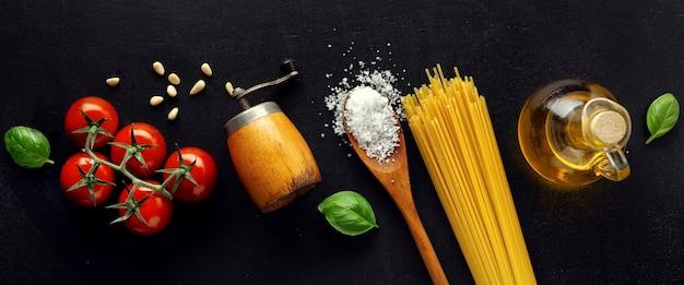 Traditioneel italiaans eten met de kaasolijven van spaghettitomaten en olie op donker