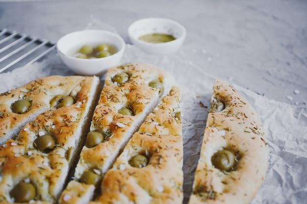 Traditioneel italiaans focaccia brood met olijven, rozemarijn, zout en olijfolie