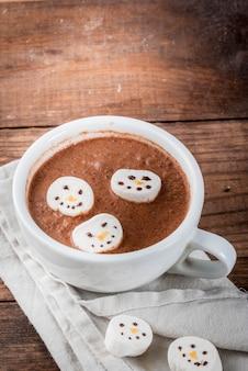 Traditioneel kerstdrankje idee. warme chocolademok met marshmallow, versierd in de vorm van sneeuwmannen, op houten tafel
