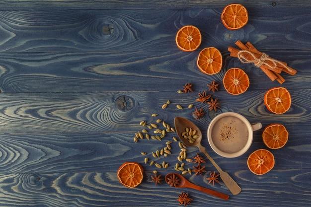 Traditioneel kerstmiskader met kruiden en geassorteerde noten die met droge sinaasappel copyspace op een rustieke houten achtergrond voor uw kerstmisbericht worden verfraaid