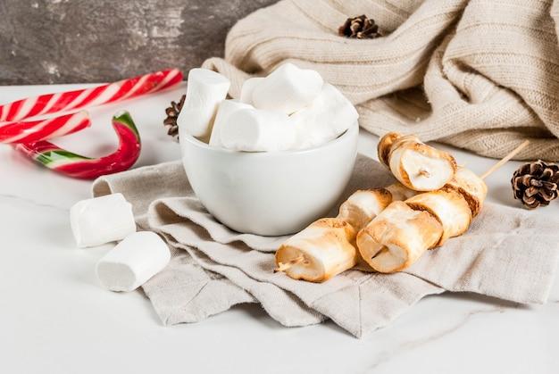 Traditioneel kerstmissnoepjes snoepriet, marshmallow en gebakken op brand marshmallow spiesjes op wit, copyspace
